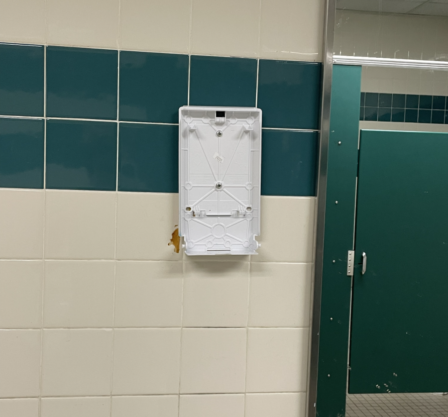 A broken paper towel dispenser and tile in a school bathroom.  Iamreallygoodatcheckers, CC BY-SA 4.0 , via Wikimedia Commons